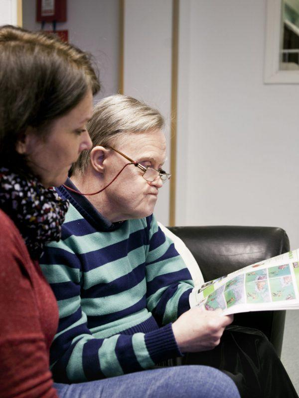 Caregiver looking at mentally challenged senior man reading magazine at home