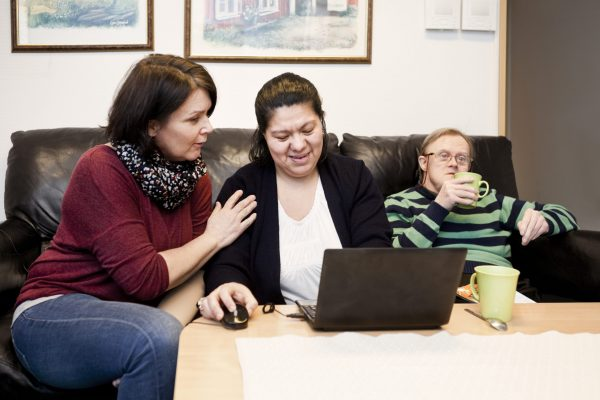 Healthcare worker helping woman with down syndrome in using laptop while man having drink at sofa