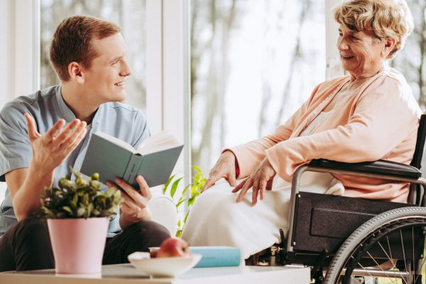 Older disabled woman on wheelchair spending time with male caregiver